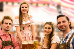 La serveuse livre des bières dans la tente avec les visiteurs heureux dans une tente de bière à Munich Oktoberfest Photos stock