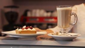 La serveuse met le gâteau à côté du latte sur la barre Machine de café à l'arrière-plan Fin vers le haut clips vidéos
