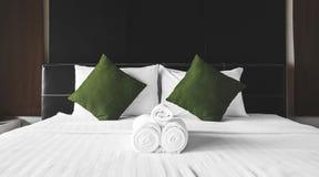 La serviette roule avec les oreillers verts sur le lit Photographie stock