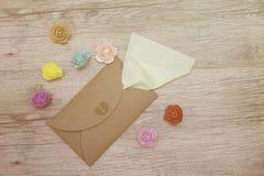 La serviette verte colle hors de l'enveloppe de métier décorée des fleurs colorées sur le bois Image plate de studio de configura Photographie stock