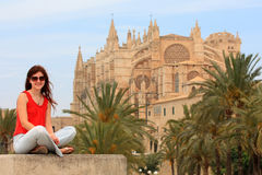 La Seu Cathedral in Palma de Mallorca. Young white woman sitting in front of the beautiful cathedral in Palma, Mallorca Stock Photography