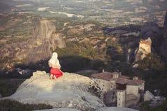 La seule fille dans une robe et une écharpe rouges s'assied au bord de la roche et prie aux monastères de Meteora Femelle sur la  Image libre de droits