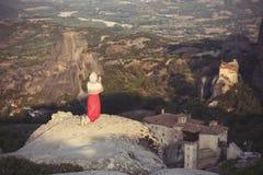 La seule fille dans une robe et une écharpe rouges s'assied au bord de la roche et prie aux monastères de Meteora Femelle sur la  Photographie stock libre de droits