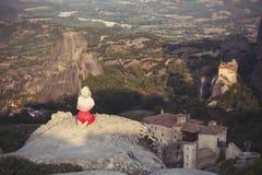 La seule fille dans une robe et une écharpe rouges s'assied au bord de la roche et prie aux monastères de Meteora Femelle sur la  Photos stock