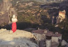 La seule fille dans une robe et une écharpe rouges s'assied au bord de la roche et prie aux monastères de Meteora Femelle sur la  Photo libre de droits