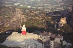 La seule fille dans une robe et une écharpe rouges s'assied au bord de la roche et prie aux monastères de Meteora Femelle sur la  Images libres de droits