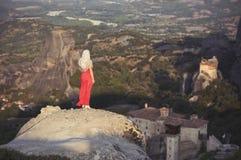 La seule fille dans une robe et une écharpe rouges s'assied au bord de la roche et prie aux monastères de Meteora Femelle sur la  Image stock