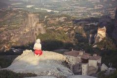 La seule fille dans une robe et une écharpe rouges s'assied au bord de la roche et prie aux monastères de Meteora Femelle sur la  Photographie stock