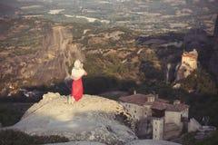 La seule fille dans une robe et une écharpe rouges s'assied au bord de la roche et prie aux monastères de Meteora Femelle sur la  Photo stock