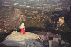 La seule fille dans une robe et une écharpe rouges s'assied au bord de la roche et prie aux monastères de Meteora Femelle sur la  Photos libres de droits