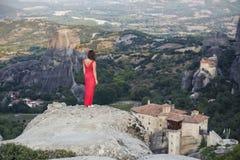 La seule fille dans une robe rouge au bord de la roche et prie aux monastères de Meteora Femelle sur la roche et le m Photo libre de droits