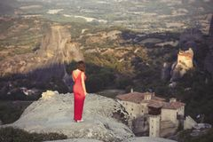 La seule fille dans une robe rouge au bord de la roche et prie aux monastères de Meteora Femelle sur la roche et le m Images libres de droits