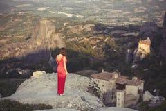 La seule fille dans une robe rouge au bord de la roche et prie aux monastères de Meteora Femelle sur la roche et le m Images stock