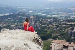 La seule fille dans une robe rouge s'assied au bord de la roche et prie aux monastères de Meteora Femelle sur la roche et le m Photographie stock