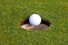 La sfera di golf sta andando in un foro Fotografie Stock