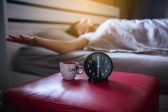 La sfuocatura della donna asiatica sveglia l'allungamento e sbadiglia sulla camera da letto con la sveglia nera Immagine Stock
