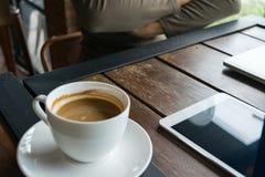 La sfuocatura qualcuno in caffetteria ha il caffè, il blocco note e computer portatile sopra Fotografie Stock