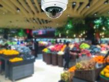 La sicurezza della macchina fotografica del CCTV nel centro commerciale con il supermercato offusca indietro immagini stock