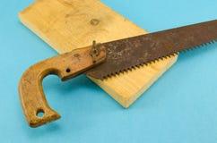 La sierra y la madera oxidadas retras de la mano suben a la parte en azul Imagenes de archivo