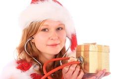 La sig.na Santa sta sondando un contenitore di regalo dorato Fotografia Stock