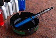 La sigaretta elettronica sul portacenere e le bottiglie con il liquido del vape su granito sorgono Fotografia Stock Libera da Diritti