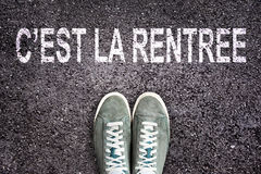 La signification de rentree de La d'est de ` des mots C de nouveau à l'école écrite sur la route goudronnée avec des chaussures d Photos stock