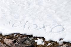 La signification de Xoxoxo étreint et des baisers écrits dans la neige Photographie stock libre de droits