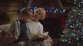 La signora anziana legge un libro al suo nipote nella notte di Natale e chiede il suo qualcosa stock footage