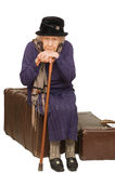 La signora anziana si siede su una valigia Fotografia Stock