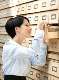 La signora graziosa cerca qualcosa nel catalogo di scheda Fotografia Stock Libera da Diritti