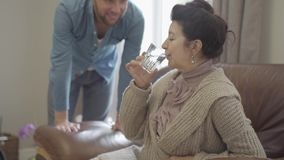 La signora matura che si siede sulla poltrona di cuoio a casa Il nipote adulto porta il bicchiere d'acqua e lo dà al stock footage