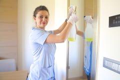 La signora sta pulendo lo specchio Fotografia Stock Libera da Diritti
