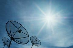La silhouette, antenne parabolique sur le ciel bleu avec le soleil lumineux rayonne briller, fond d'image réseau de technologie d Images stock