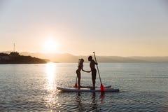 La silhouette d'embrasser le mâle et la femelle sur la petite gorgée surfent à l'océan Mode de vie de concept, sport, amour Image stock
