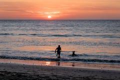 La silhouette d'homme et de chien au beau coucher du soleil dans Mancora échouent - Mancora, Pérou Photographie stock libre de droits