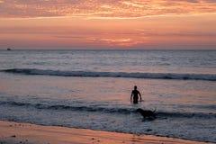 La silhouette d'homme et de chien au beau coucher du soleil dans Mancora échouent - Mancora, Pérou Photos stock