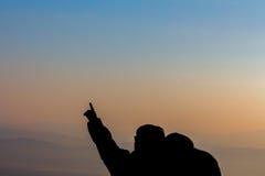 La silhouette d'un couple dans l'amour voyagent, ciel opacifié Photographie stock