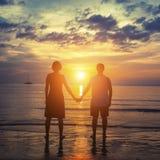 La silhouette d'un couple sur leur lune de miel se tenant sur l'océan échouent au coucher du soleil étonnant Photo stock