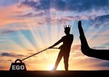 La silhouette d'un homme égoïste avec une couronne sur sa tête dessine une charge lourde - l'amour-propre et un grand arrêt de ma Photo libre de droits