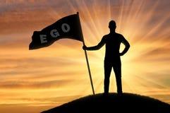 La silhouette d'un homme égoïste avec une couronne sur sa tête tient un drapeau avec l'amour-propre de mot sur une colline Images stock