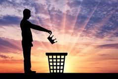 La silhouette d'un homme jette une couronne dans la poubelle de déchets Photo libre de droits
