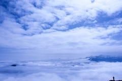 La silhouette d'un homme qui regarde le ciel couvert de nuage sur t images stock