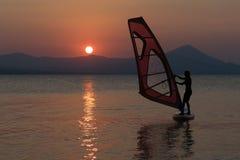 La silhouette d'une belle femme surfant avec elle font de la planche à voile contre le soleil Image libre de droits
