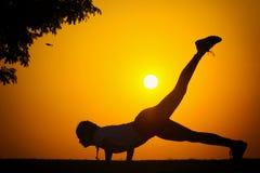 La silhouette d'une fille qui exercent la forme physique Photos stock