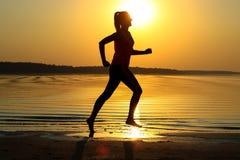 La silhouette d'une jeune belle fille fonctionne le long du bord de la mer sur le fond orange de coucher du soleil photo libre de droits