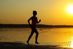La silhouette d'une jeune belle fille fonctionne le long du bord de la mer sur le fond orange de coucher du soleil photos libres de droits