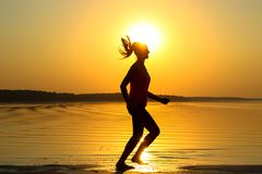 La silhouette d'une jeune belle fille fonctionne le long du bord de la mer sur le fond orange de coucher du soleil image stock