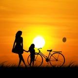 La silhouette d'une mère et d'une fille pendant le coucher du soleil Photographie stock