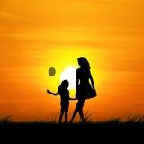 La silhouette d'une mère et d'une fille pendant le coucher du soleil Photos libres de droits