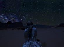 La silhouette d'une personne montant le chameau sous les étoiles, la manière laiteuse et beaucoup d'étoiles au-dessus de la monta Images libres de droits